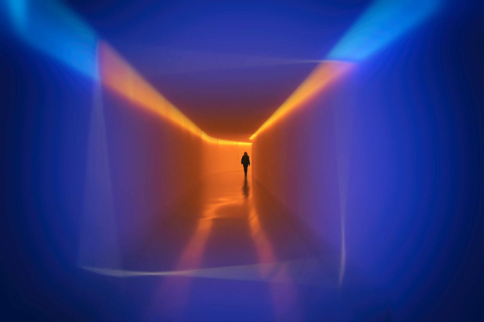Man walking in blue and orange corridor