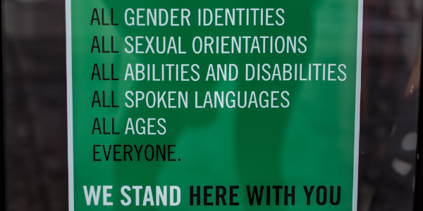 green sign that talks about inclusivity